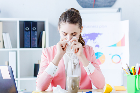 Young beautiful business woman boss feeling sick and tired while sitting at her workplace and drinking tea with lemon. Exhausted girl employee with flu, headache and runny nose working in office.