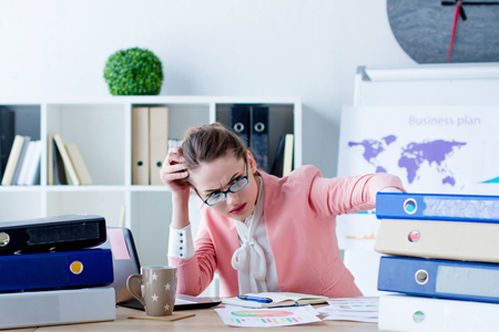 Young beautiful business woman boss  in glasses is working focused with documents at her workplace. Girl employee frowning looking at bunch of folders at modern office. Work hard concept.