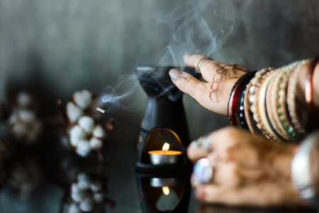 Female wrists painted with henna traditional Indian oriental mehndi ornaments. Hands dressed in metal bracelets and rings holding aromatic stick. Aroma lamp and cotton flowers on background. Stok Fotoğraf