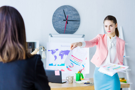 Young beautiful boss in pink blazer is doing reprimand to employee. Strict furious brunette business woman is having meeting with colleague in modern light office. Stress at job concept.