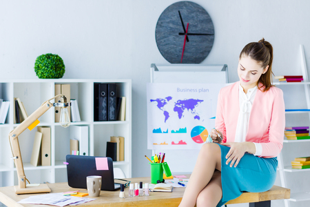 Young lazy business woman in pink blazer is idling at workplace. Beautiful girl employee is painting nails with polish sitting on desk in modern office. Relax time at job. Bad worker concept.