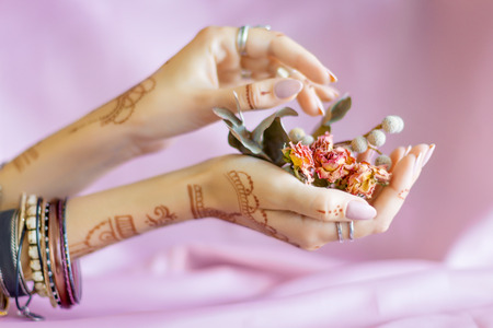 Slender elegant female wrists painted with traditional Indian oriental mehndi ornaments by henna. Hands dressed in bracelets and rings hold dry roses flowers. Pink fabric with folds on background. Stok Fotoğraf