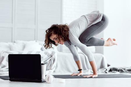 Young happy healthy fitness beautiful woman female doing bakasana yoga posture and workout on yoga mat opposite laptop with online master class at modern bedroom at home. Healthy lifestyle concept