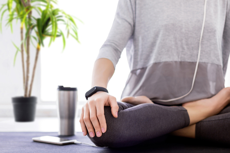 Closeup of slender female legs folded crossed in lotus position. Young athletic woman in grey clothes and fitness tracker is practicing yoga, meditating, relaxing while sitting in padma asana at home.