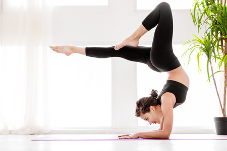 Young healthy fitness beautiful woman female doing vrischikasana yoga posture and yoga workout on yoga mat at yoga studio in morning. Healthy lifestyle, morning workout concept Stok Fotoğraf