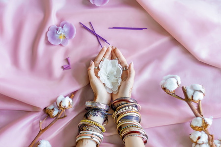 Female wrists painted with traditional Indian oriental mehndi ornaments by henna. Hands dressed in bracelets and rings hold white flower. Pink fabric with folds and cotton branches on background.