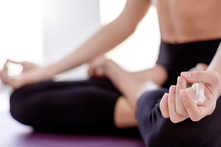 Closeup of slender female legs folded crossed in lotus pose. Young athletic girl in black uniform is practicing yoga, meditating, relaxing while sitting in padma asana. Woman keep balance and harmony. Stok Fotoğraf
