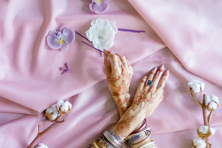 Female wrists painted with traditional Indian oriental mehndi ornaments. Hands dressed in bracelets and rings hold aroma stick. Pink fabric with folds, cotton branches and candles on background.