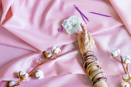 Slender female hand painted with Indian oriental mehndi ornaments by henna. Hand dressed in bracelets and rings hold white flower. Light pink fabric with folds and cotton branches on background. Stok Fotoğraf