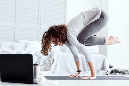 Young happy healthy fitness beautiful woman female doing bakasana yoga pose and workout on yoga mat opposite laptop with online master class at modern bedroom at home. Healthy lifestyle concept. Stok Fotoğraf