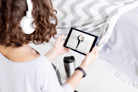 Back view of brunette female in headphones sitting on sport mat in lotus position and watching fitness tutorial lesson on tablet. Young athletic woman in fitness tracker is practicing yoga at home.