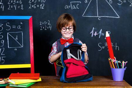 Aufgeregter intelligenter Schüler, der bereit ist, im Klassenzimmer in der Schule zu lernen. Schulbezogene Gegenstände vorbereiten: Bleistifte, Notizbücher und Schulrucksack gegenüber Tafel mit mathematischen Formeln. Zurück zum Schulkonzept