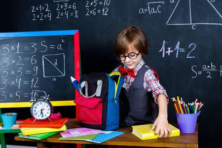 Excited smart schoolboy ready to study at school in classroom. Preparing school related objects: pencils, notebooks and school backpack opposite chalkboard with math formulas. Back to school concept Imagens