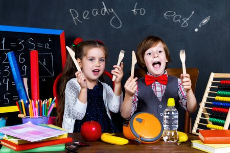 Excited smart schoolboy and schoolgirl ready to have lunch: apple, banana and water at school. School related objects: chalkboard with math formulas, pencils and notebooks. Back to school concept