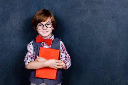Niño colegial inteligente inteligente con anteojos y lazo rojo que sostiene el libro de estudio rojo frente a la pizarra de la escuela en la escuela. Regreso a la escuela, listo para estudiar el concepto