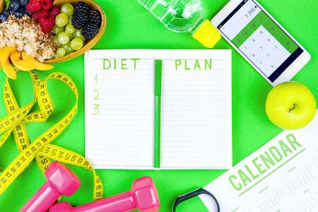 Fitness diary for training and planning healthy lifestyle. Calendar, pink fitness weights rack, meusure tape, smartphone with calculator and raw healthy diet food. Healthy lifestyle concept.