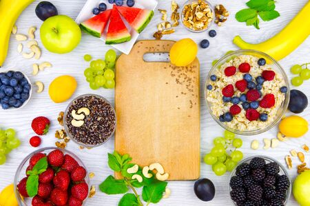 Raw healthy food: banana, berries: strawberry, blackberry, raspberry, grape with quinoa and cashew nuts for breakfast isolated on white background. Healthy, fitness, diet and raw food to go concept. Stock Photo