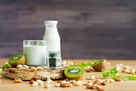Organic summer breakfast with superfood spirulina, yogurt, kiwi, mint and nuts on wooden table. Meal that promotes good digestion and functioning of gastrointestinal tract. Healthy food concept. Banque d'images