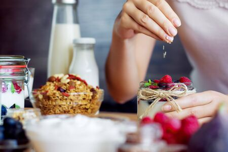 Female hands cooking low calorie healthy dietary vegetarian breakfast. Natural organic yoghurt with berries, goji, nuts, figs, granola and fruits for good digestion on table. Healthy food concept.