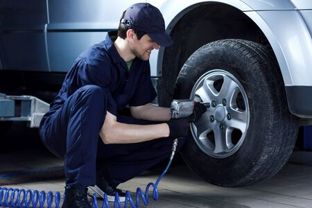 Smiling mechanic in blue jumpsuit is repairing car at service station garage. Repairman is removing wheel by electric wrench, tyre mounting equipment at workshop auto repair shop. Tire fitting concept Reklamní fotografie