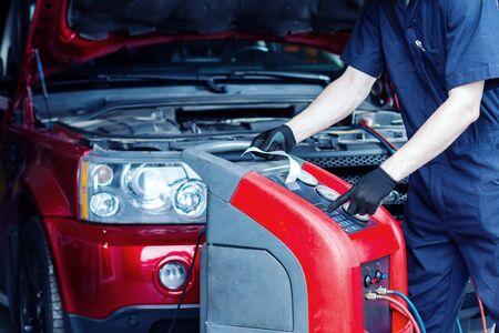 Le mécanicien répare la voiture à la station-service. Le réparateur en combinaison effectue des diagnostics. Le véhicule est connecté à l'équipement pour l'entretien et le ravitaillement des climatiseurs dans l'atelier de réparation automobile.