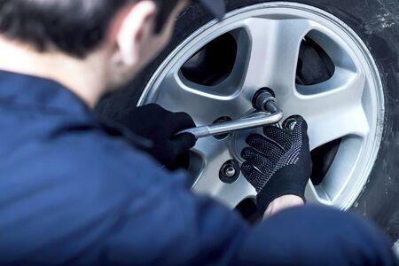 青いジャンプスーツを着たバックビューメカニックがサービスステーションで車を修理しています。クローズアップ修理工の手は、自動車修理工場でホイールを取り外すためにレンチでディスク上のナットを緩めている。タイヤフィッティングコンセプト。