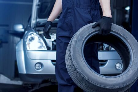 Mechanik w niebieskim kombinezonie naprawia samochód na stacji obsługi. Zbliżenie mechanik ręce trzymają oponę z koła w warsztacie. Pojazd z otwartym kapturem na tle. Koncepcja montażu opon. Zdjęcie Seryjne
