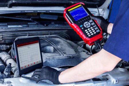 Primo piano dello schermo del laptop con software speciale, equipaggiamento del veicolo con cofano aperto. Il riparatore sta conducendo la diagnostica e rilevando i problemi in officina. Il meccanico sta riparando l'auto alla stazione di servizio.