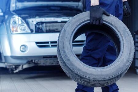 Mechanic in blue jumpsuit is repairing car at service station. Closeup of repairman hands are holding tyre from wheel in workshop. Vehicle with open hood on background. Tire fitting concept.