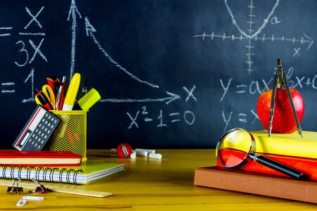 Mathematic classroom at school. Math formulas drawn at chalkboard. School supplies: physics books, pens, rulers and magnifying glass on wooden desk. Back to school and ready to study concept