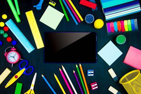 Back to school, college, university. Blue tablet computer in center of blackboard background. Office supplies, pencils, markers, scissors, sharpeners, rulers, alarm clock are scattered on canvas. Stock Photo
