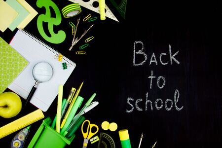 Chalk inscription of back to school on blackboard background. Green and yellow office supplies, pensils, pens, rulers, scissors are scattered on left side of black canvas. Preparing pupils for study. Stock Photo