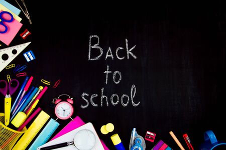 Chalk inscription of back to school on blackboard background. Blue, yellow and pink office supplies, pens, rulers, scissors, alarm clock are scattered on left side of black canvas. Preparing for study