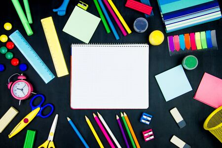 Back to school, college, university. White page of notebook in center of blackboard background. Office supplies, pencils, scissors, sharpeners, plasticine, alarm clock are scattered on black canvas.