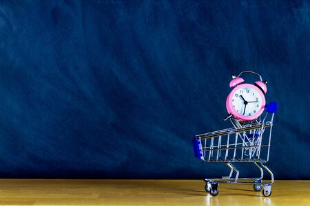 School and study supplies in shopping cart, trolley: pink alarm on wooden desk and chalkboard background. Back to school and ready to study concept.