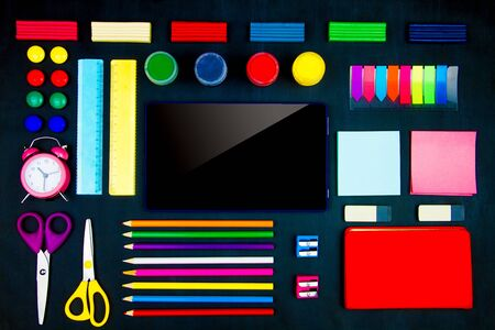 Colorful office supplies neatly geometrically evenly laid out on blackboard background. Pencils, scissors, sharpeners, plasticine, alarm clock, tablet on canvas. Preparing perfectionist for study. Stock Photo