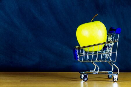 School and study supplies in shopping cart, trolley: green apple on wooden desk and chalkboard background. Back to school and ready to study concept.