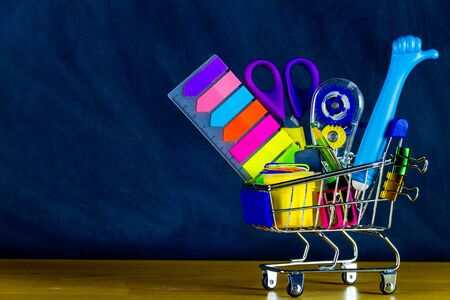 School and study supplies in shopping cart, trolley: notebooks, sticky notes, pens, scissor, ruler and apple on wooden desk and chalkboard background. Back to school and ready to study concept.