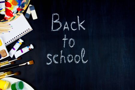 Chalk inscription of back to school on blackboard background. Colorful painting supplies, tools, paper, pencils, paints, brushes, watercolors, palette are scattered on left side of canvas.
