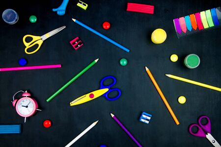 Back to school, college, university. Office supplies on blackboard background. Pencils, scissors, sharpeners, plasticine, alarm clock are scattered on black canvas. Preparing pupil child for study.