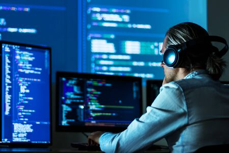 Software developer freelancer man male in headphones work with program code C++ Java Javascript on wide displays at night Develops new web desktop mobile application or framework. Projector background Stockfoto