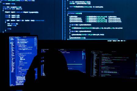 Unknown software developer freelancer work with program code C++ Java Javascript on wide displays at night Develops new web desktop mobile application or framework Projector futuristic background