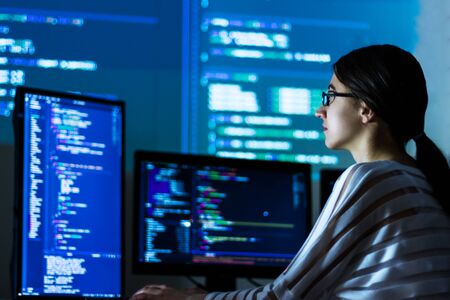 Software developer freelancer woman female in glasses work with program code C++ Java Javascript on wide displays at night Develops new web desktop mobile application or framework Projector background Stockfoto