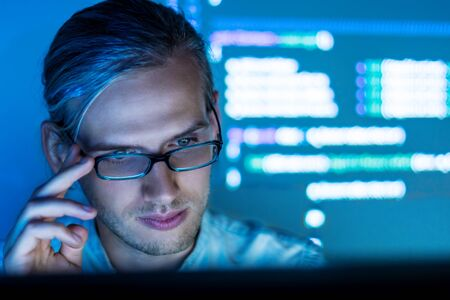 Software developer freelancer in glass work with program code C++, Java, Javascript on wide displays at night. Develops new web desktop mobile application or framework. Projector futuristic background