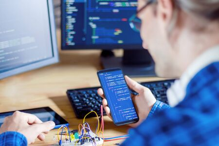 Developer is connecting breadboard to microcontroller. Man is holding smartphone with program code software for controlling electronic device. Chips, resistors, diodes on desktop of hardware engineer.