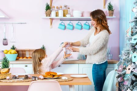 Smiling woman and little cute girl are cleaning light christmas kitchen. Happy mother and daughter are serving table with dishes. Family are preparing for festive dinner, celebration of new year. Stock Photo
