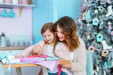 Smiling woman and little girl child are sitting at table in light christmas kitchen. Mom and daughter are packing presents with colorful paper. Family preparation for celebration happy new year.