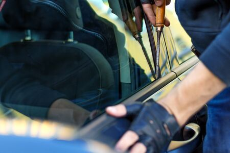 Closeup male hands in black gloves is trying to open, break into automobile without signaling alarm. Burglar, thief is hacking door lock of private auto. Theft in car concept. Bad parking security. Stockfoto