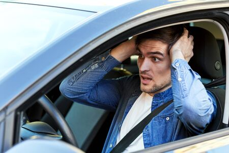 Shocked excited young man is driving car. Driver in denim shirt have accident crash with other road users. Brunette male is violating rules and laws. Stressful emergency situations on routes in city.