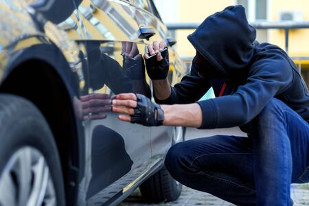 Bully in black stocking on face and hood is scratching automobile with nail. Bandit is spoiling appearance of private car. Man is making scratch on auto without signaling. Vandalism act concept. Stock fotó